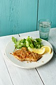 Veal escalope with a hazelnut crust served with young lettuce leaves