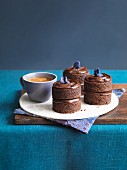 chocolate fudge cakes with candied violets and coffee