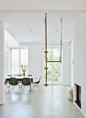 Essbereich mit grünen Schalenstühlen und Kletterseil von Decke abgehängt, in minimalistischem, weißem Raum