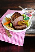 Roasted wild boar with vegetables and cranberries