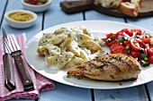 Grilled chicken breast with potato salad and tomato salad