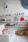 Weisser Sessel neben weisser Holzwand, Bücher & Dekoobjekte auf Ablagen, darüber alte Kukucksuhr an Wand