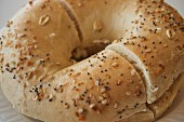 A sesame and poppy seed bagel with butter, sliced