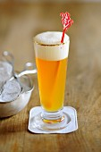 A glass of wheat beer on a wooden table