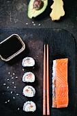Maki-Sushi mit Lachs, Avocado, Ingwer, Sojasauce und Stäbchen