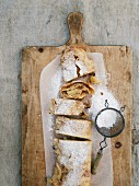 Apple strudel with an icing sugar sieve on a wooden board