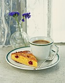 A slice of almond tart with raspberries served with a cup of coffee
