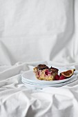 A slice of millet cake with figs, raspberries and nuts