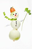 A snowman made from onions, carrots and parsley