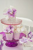 White and purple hydrangea flowers in white metal containers on a glass cake stand