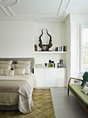 Teilweise sichtbares, elegantes Doppelbett mit drapierten Kissen, neben in Nische eingebaute Unterschränke in Weiß, auf Ablage stilisierte Trophäe, in traditionellem Schlafzimmer