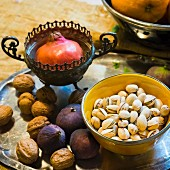 An oriental arrangement of pistachios, pomegranates, walnuts and figs