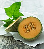 Galia melon, halved, with leaves