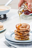 A stack of pancakes being drizzled with maple syrup