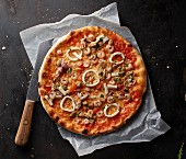 Frutti de Mare pizza on a piece of paper with a knife