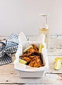 Smoked chicken wings with lime wedges