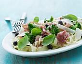 Pasta salad with raw ham, broccoli, Parmesan and basil