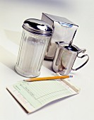 An order pad, a pencil, a sugar shaker, a jug of cream and a napkin dispenser