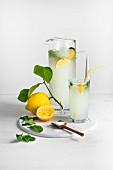 Hausgemachte Limonade mit Zitronen und Holzlöffel mit Zucker