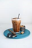 Ein Glas Haselnuss-Eiskaffee, brauner Zucker und Hippenröllchen