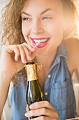 A cheerful young woman sipping champagne from a bottle