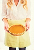 A woman holding a pumpkin pie
