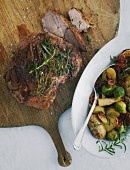 Leg of lamb with potatoes and Brussels sprouts on a large wooden board