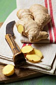 Fresh ginger on a tea towel with a knife