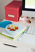 Yoghurt with raspberries, grilled apples and pistachios in a Tupperware bowl on a desk