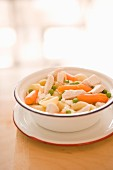 Shell pasta with chicken, carrots and peas