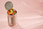 An open tin can filled with raw, diced meat and vegetables