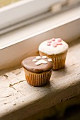 Two cupcakes decorated with pawprints made from icing sugar