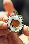 Hands holding an uramaki sushi with salmon