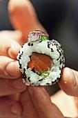 Hands holding an uramaki sushi with salmon