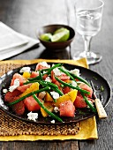 Watermelon salad with citrus fruits, green beans and feta cheese