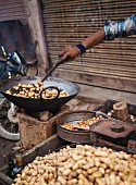 A street vendor cooking peanuts at a market in Varansi, India