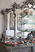Antikes Buffet mit verziertem Spiegelaufsatz, davor angerichtete Speisen