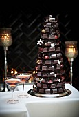 A table laid for Christmas with a Christmas tree sculpture made from chocolate curls with two glasses of rosé wine next to it