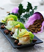 Scallops with orange fillets wrapped in lettuce leaves served with roasted almonds