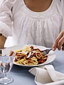 A woman eating spaghetti bolognese