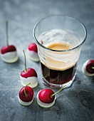An espresso and cherries with white chocolate