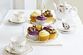 Verschiedene Cupcakes auf einer Etagere zwischen Teegeschirr