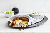 Fish and chips wrapped in newspaper served with tartare sauce and peas