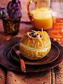 A baked apple with raisins, orange zest and vanilla sauce