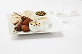 Kofta and falafel with pita bread, hummus and tomato salad