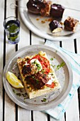 Lamb kofta with tomatoes, yoghurt and parsley on unleavened bread