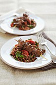 Marinated lamb skewers with grilled tomatoes, rice and lentils