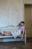 Junge Frau im Rock und Pullover relaxt auf Bank