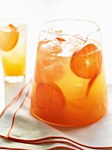 A jug of of fresh orange juice with ice cubes