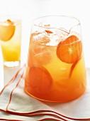 Krug mit frischem Orangensaft und Eiswürfeln
